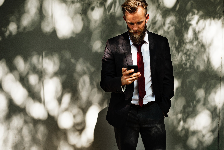 bearded man looking at phone