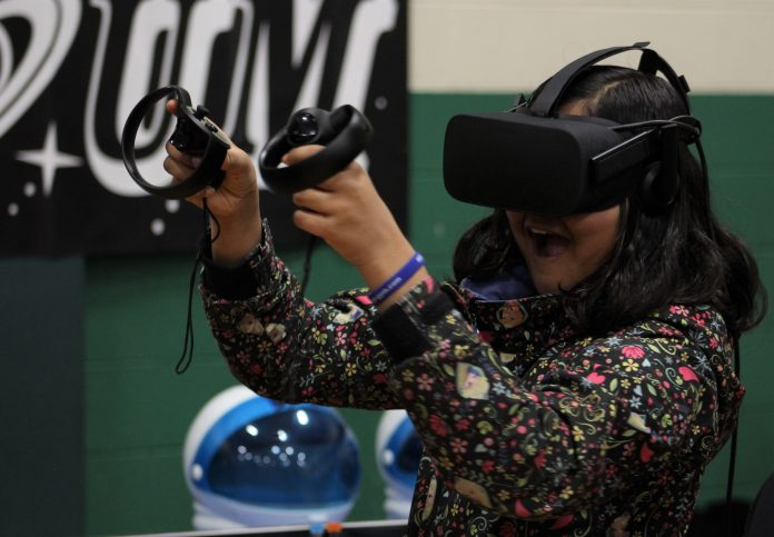 Child playing with a VR headset and smiling.